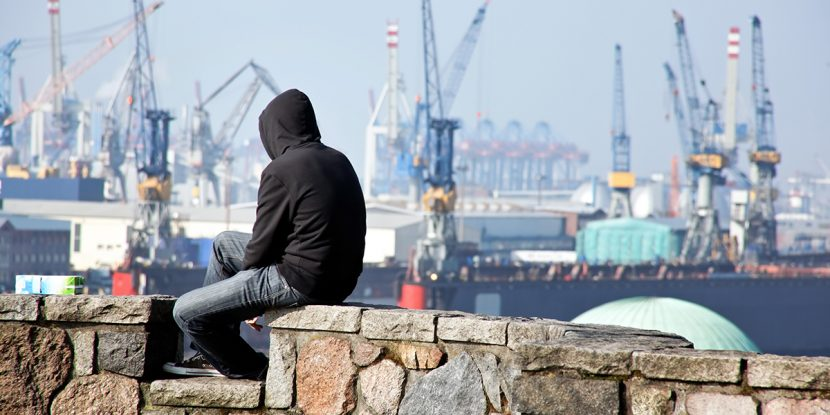A young man using a hoodie and looking at the harbor