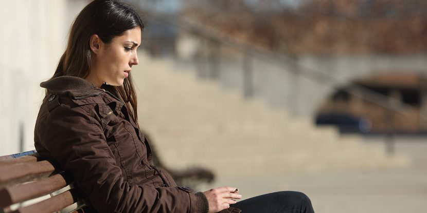 Serious young woman sitting on a bench outdoors